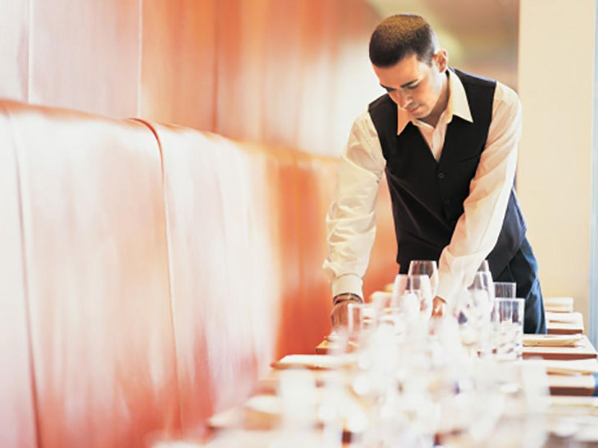 waiter server cleaning prepping table