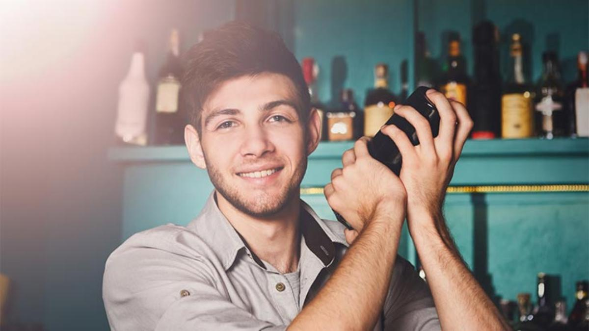 young bartender mixing cocktail