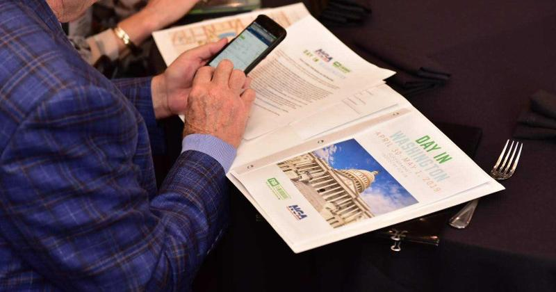 Photo: Rudy Dory, chairman, Newport Avenue Markets, checks his schedule for Day in Washington.