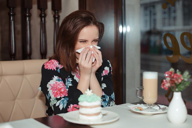 Woman sneezing in restaurant