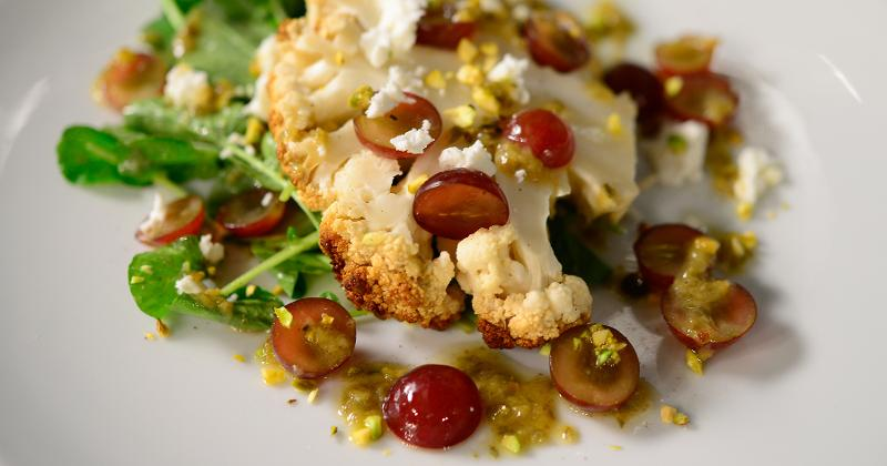 Roasted Cauliflower Steak with Grapes, Pistachios, Feta and Caper Vinaigrette