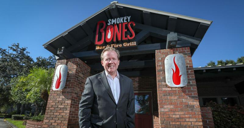 Smokey Bones CEO in front of store