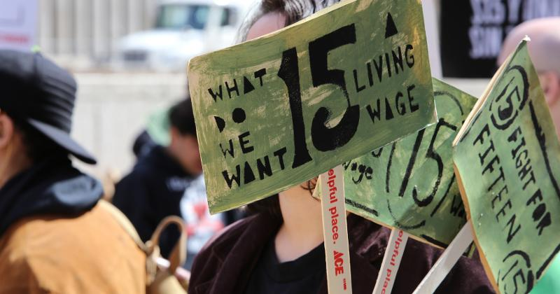 Person holds sign demanding $15 minimum wage