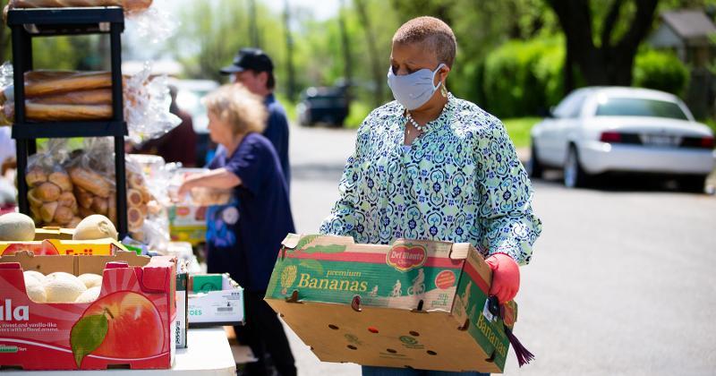 Woman moves food at food bank