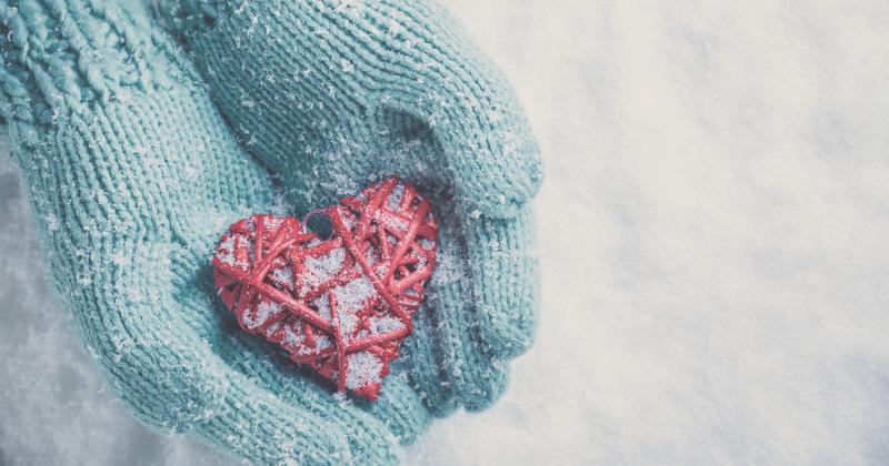Gloved hands holding snowy heart