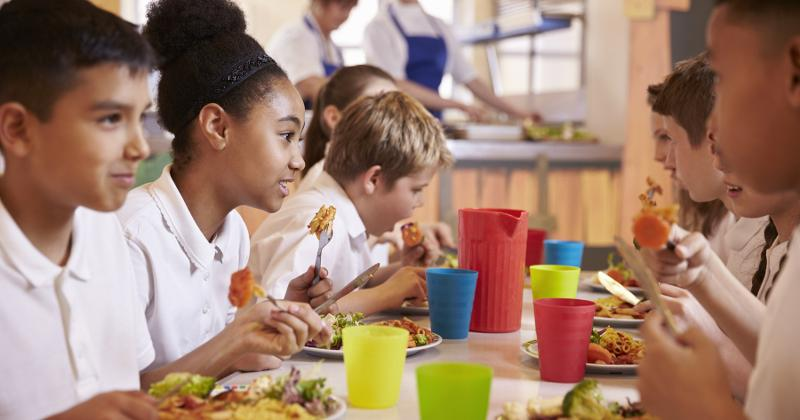 Children eating food in cafeteria.