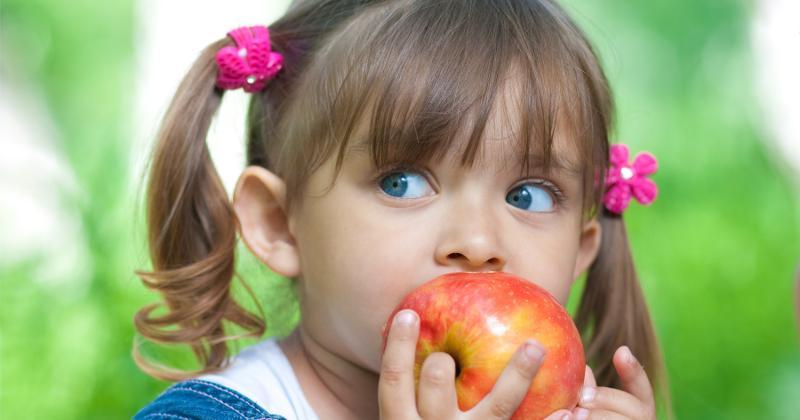 Girl eating apple outside