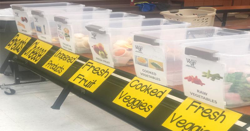 The separate bins for the leftover food to be donated lined up in the cafeteria.