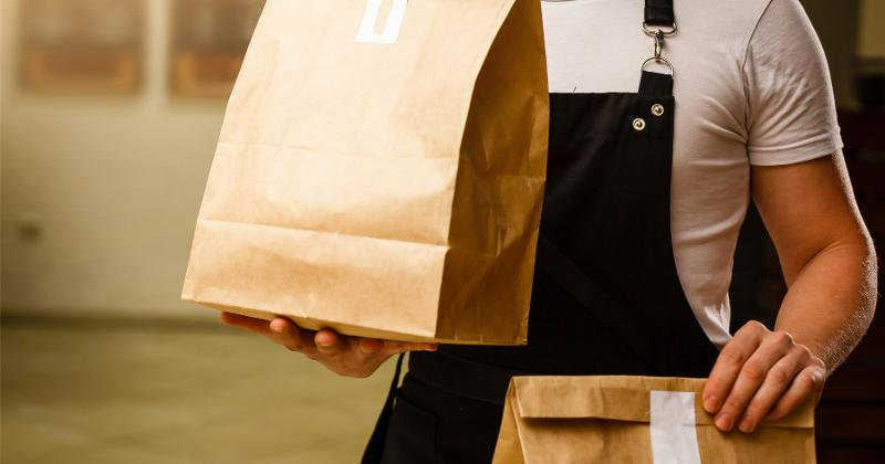 Delivery man carrying bags of food.