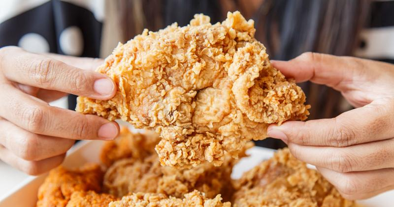 Hands holding fried chicken