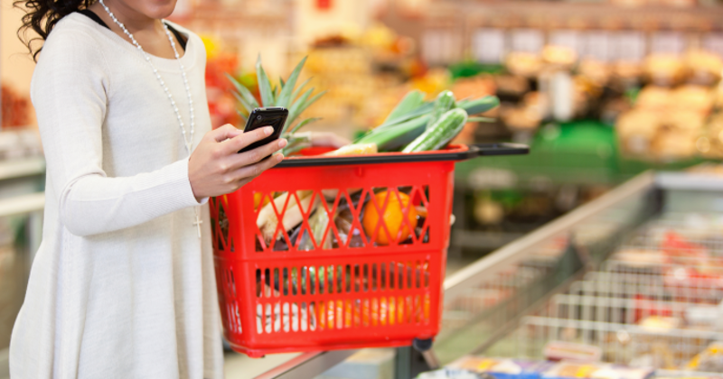 Grocery shopper uses mobile phone in store