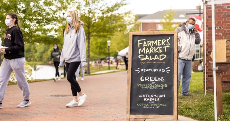 A sign advertising a farmers market salad at Elon University.