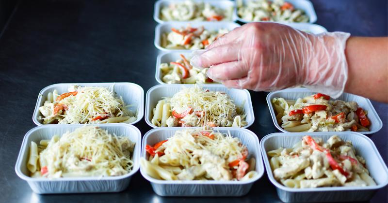 Close up of hands preparing food in to-go containers.