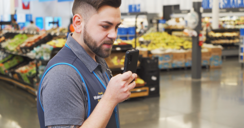Walmart associate using smartphone