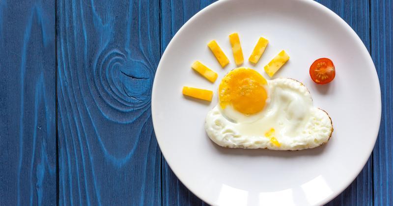 Egg shaped like the sun on a plate