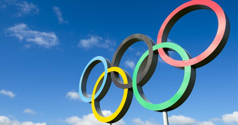 The Olympic Rings underneath a blue sky.