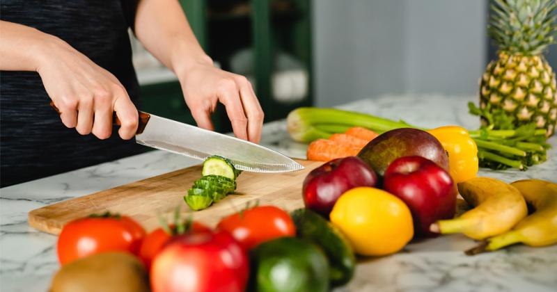 Hands cutting vegetables.