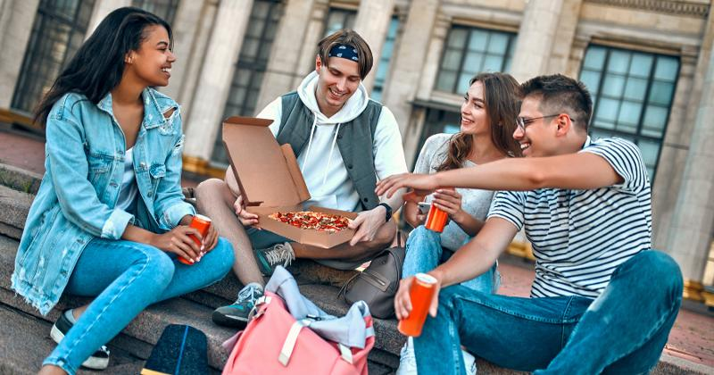 College students eating pizza together.