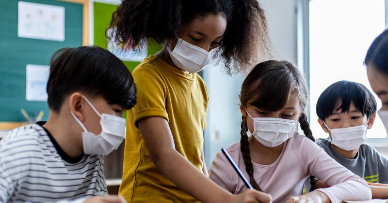 A group of students wearing masks in the classroom.