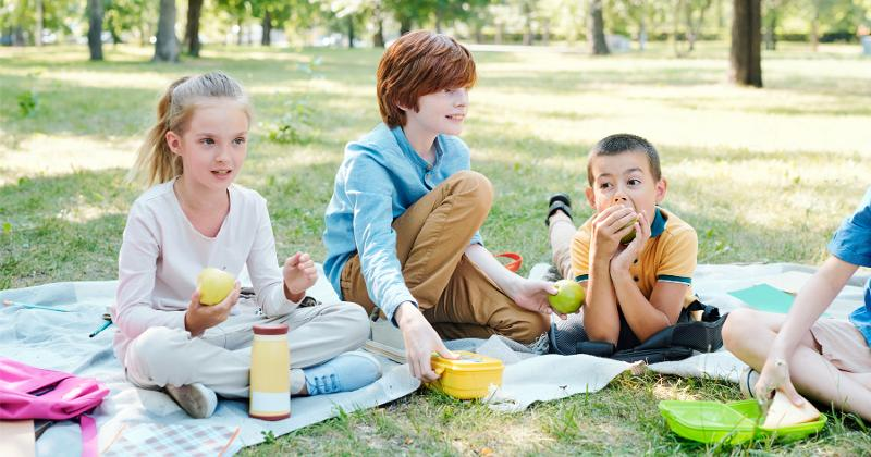 Kids sitting in the park eating lunch.