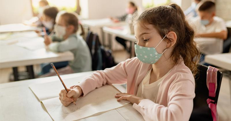 A student writing at her desk while wearing a mask.