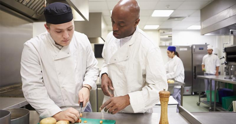 A chef in the kitchen helping out his peer.
