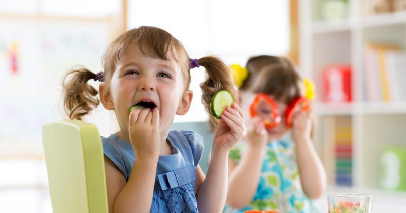 Children eating vegetables at lunch.