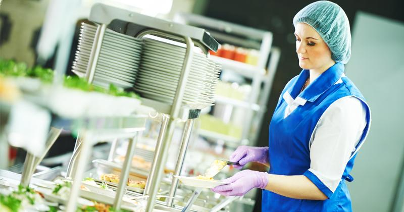 A foodservice staff member serving food in a cafeteria.
