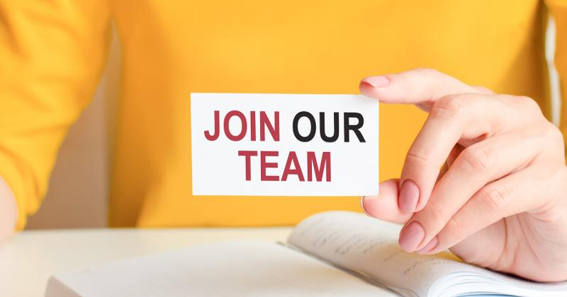 Hand holding business card that says join our team.
