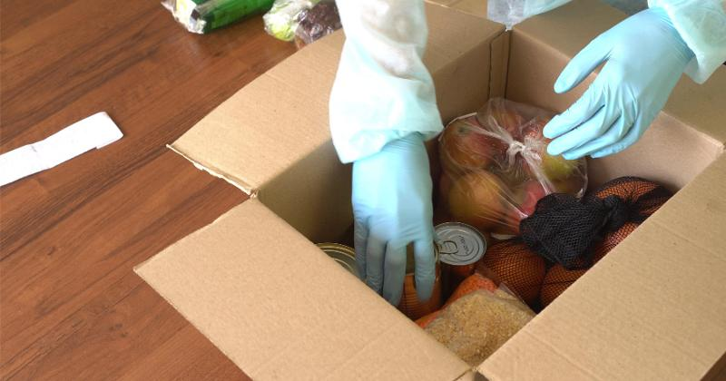 Hands packing a box of food.