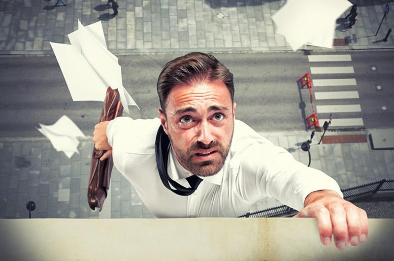 business man struggling ledge