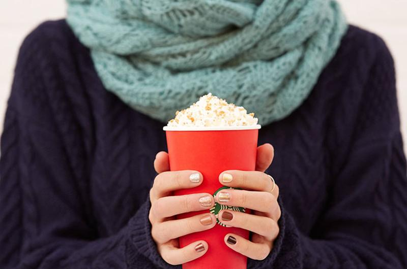 woman holding starbucks holiday drink