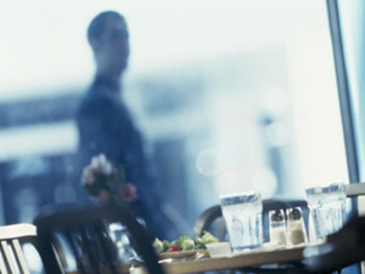 man walking past empty restaurant