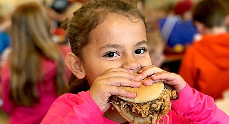 student eating pulled pork sandwich