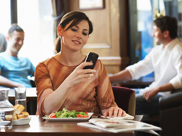 woman on phone in restaurant