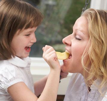 daughter feeding mom apples